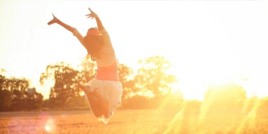 Girl jumping into the sunshine